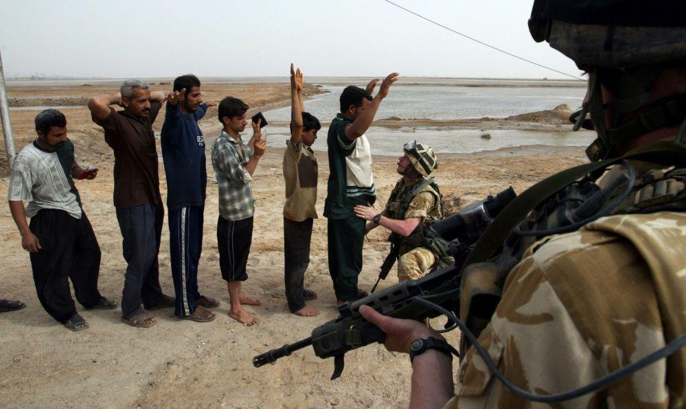 Des soldats britanniques contrôlant des Irakiens à l'entrée de la ville de Bassora.