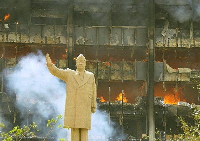 A statue of Iraqi President Saddam Hussein in front of building of the Iraqi Olympic Committee 09 April 2003. The US tanks and troops poured into the heart of Baghdad as the Iraqi leader's regime collapsed after a blistering three-week onslaught.