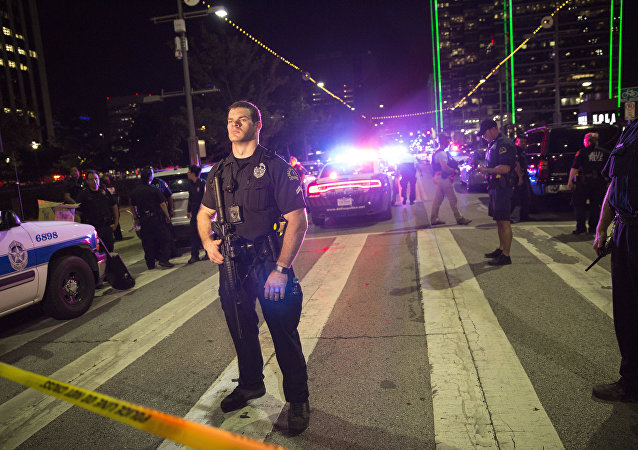 Police officers stand guard at a baracade following the sniper shooting in Dallas on July 7, 2016.