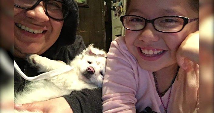 Une fille de 10 ans parle en langue des signes à son petit chien