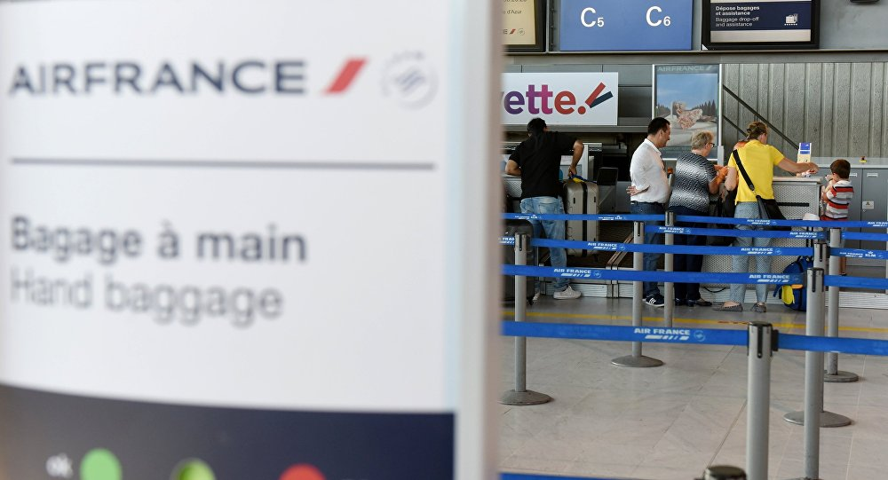 Passengers stand at an Air France desk in Nice Cote D'Azur International airport on the first day of a strike by Air France stewards, in Nice, France, July 27, 2016.