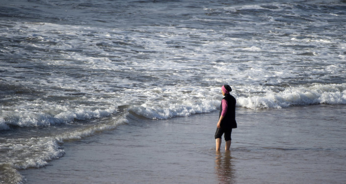 A Moroccan woman wearing a burkini, a full-body swimsuit designed for Muslim women, enters the sea at Oued Charrat beach, near the capital Rabat