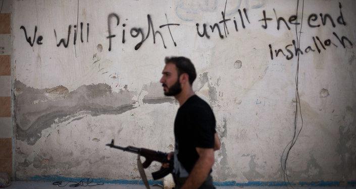 Combattant syrien en Syrie passe devant un mur