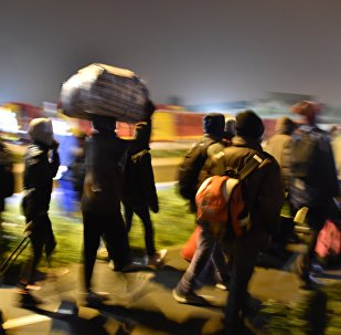 Migrants queue for transportation by bus to reception centres across France, from the Jungle migrant camp in Calais, northern France, on October 24, 2016.