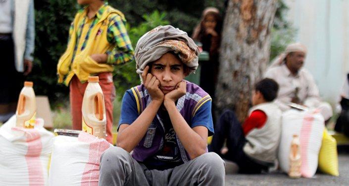 Un garçon yéménite s'assit près des approvisionnements à Sanaa