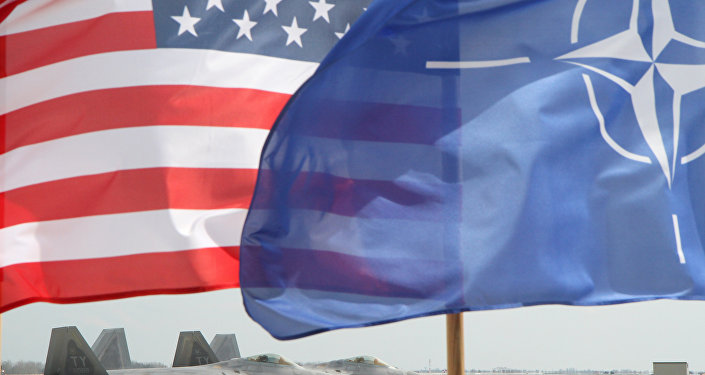 The US and The NATO flag flie in front of two US Air Force F-22 Raptor fighter aircrafts at the Air Base of the Lithuanian Armed Forces in Šiauliai, Lithuania, on April 27, 2016.