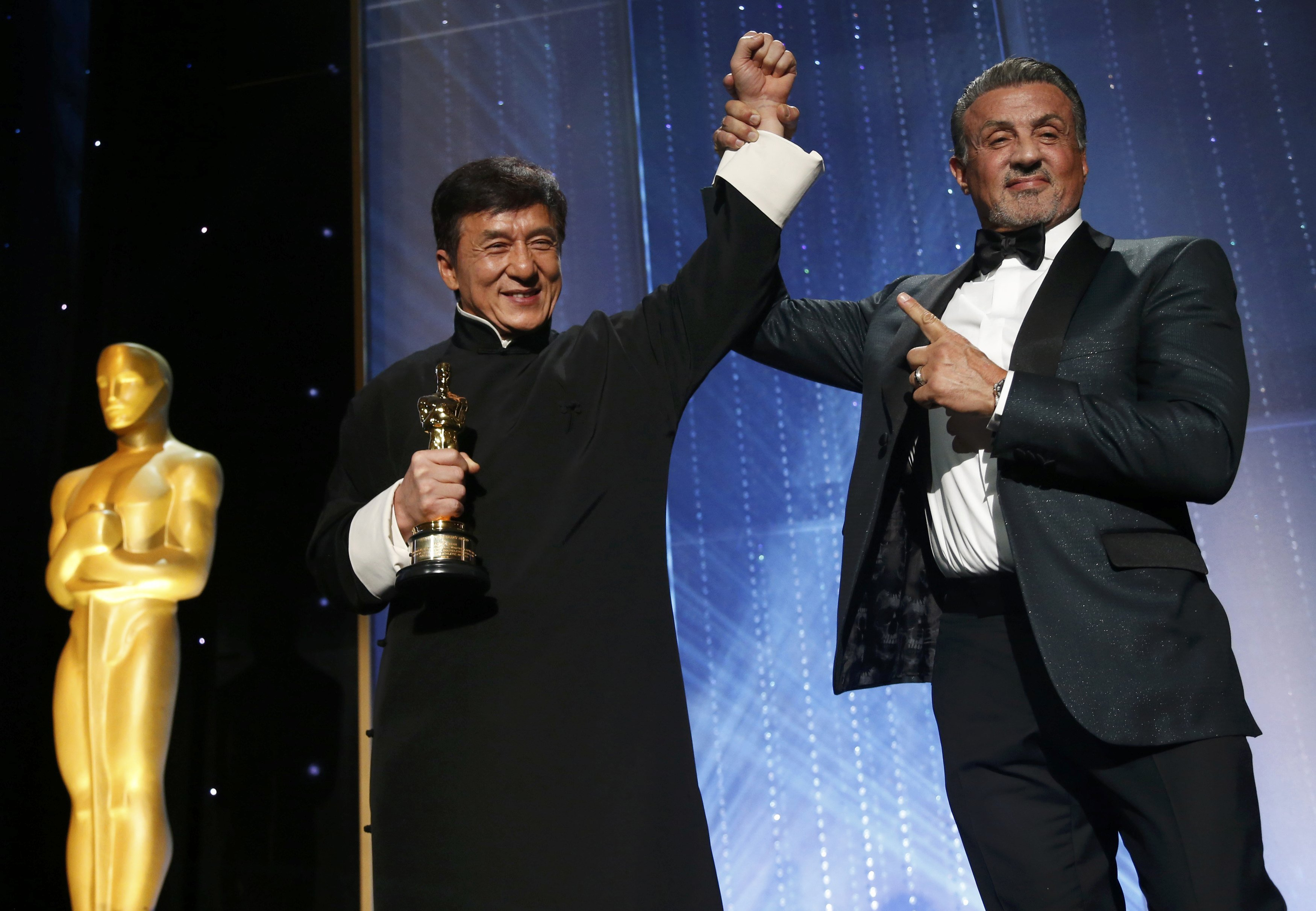 L'acteur Chan est félicité par l'acteur Silvester Stallone après avoir accepté son Oscar d'honneur lors du 8e Bal des Gouverneurs annuel à Los Angeles