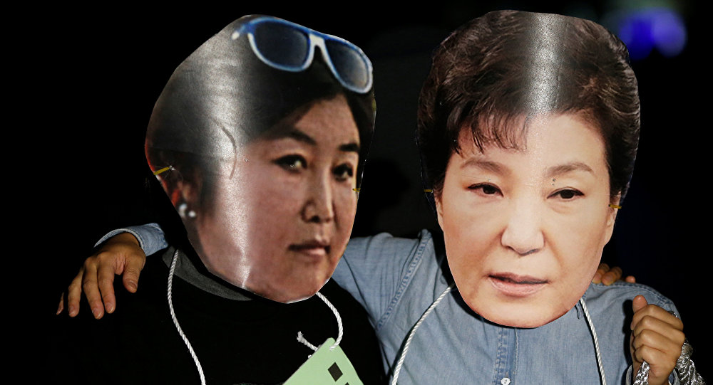 Des manifestants portent des masques à l'effigie de la présidente sud-coréenne Park Geun-hye et de sa confidente Choi Soon-sil