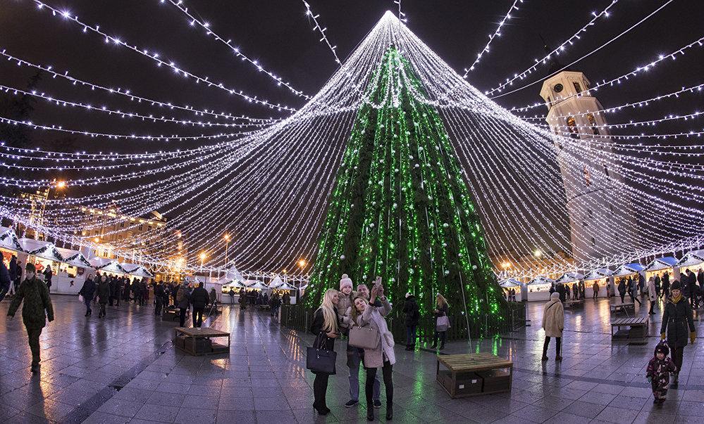 Des visiteurs prennent des photos devant le sapin de Noël sur la place de la Cathédrale à Vilnius, en Lituanie