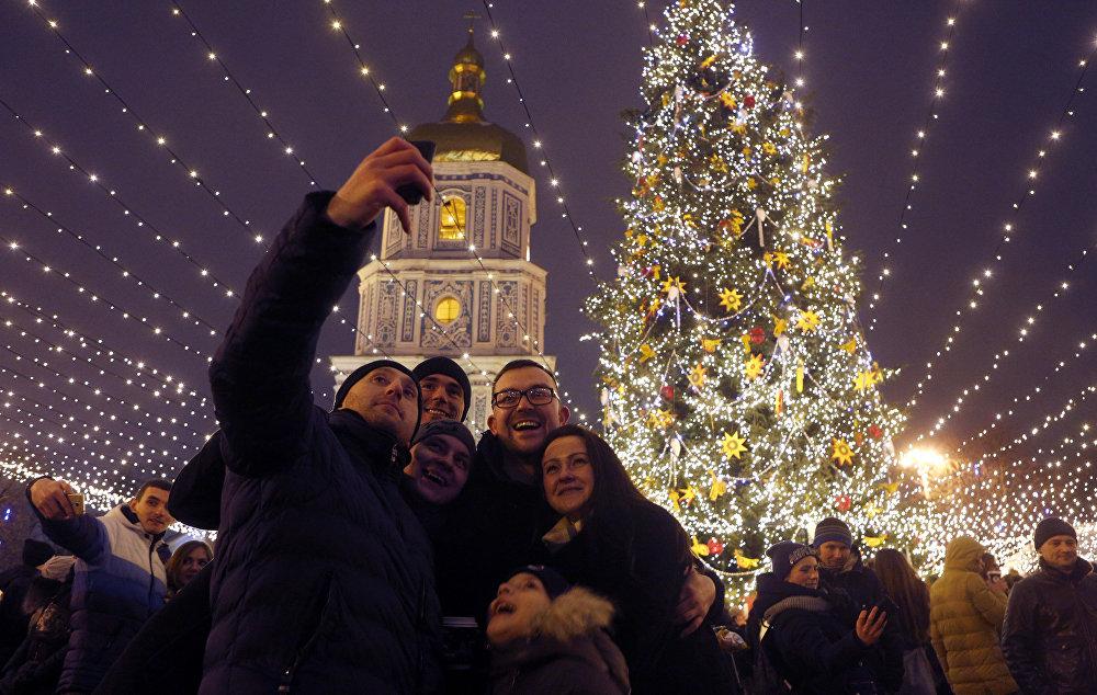 Des visiteurs prennent des photos devant le sapin de Noël près de la cathédrale Sainte-Sophie à Kiev, en Ukraine