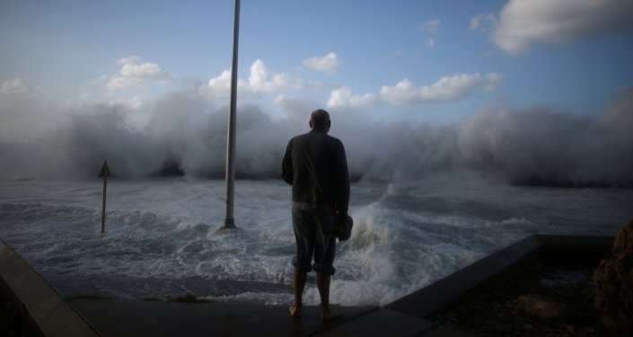 A man watches waves breaking on the Malecon seafront in Havana, Cuba, January 23, 2017