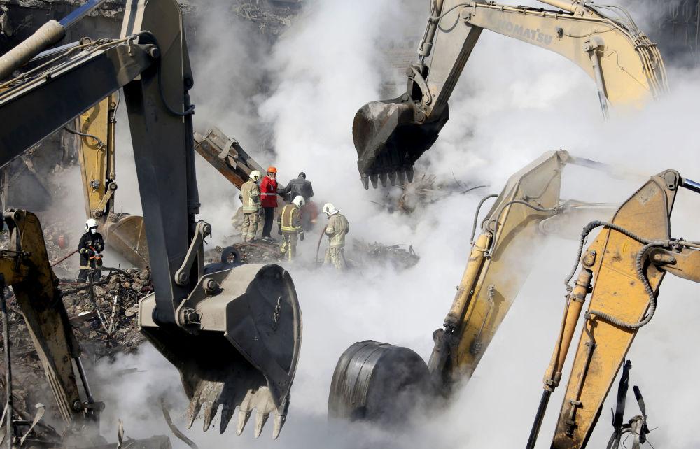 Des sauveteurs et des pompiers sur le site après l'effondrement  d'un immeuble à plusieurs étages à Téhéran, en Iran