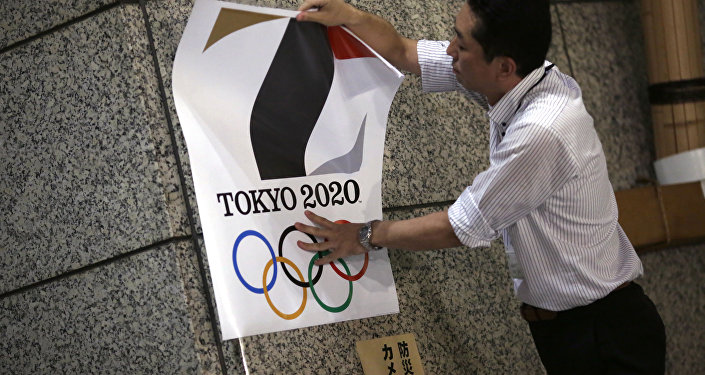 The poster with a logo of Tokyo Olympic Games 2020 is removed from the wall by a worker during an event staged for photographers at the Tokyo Metropolitan Government building in Tokyo Tuesday, Sept. 1, 2015