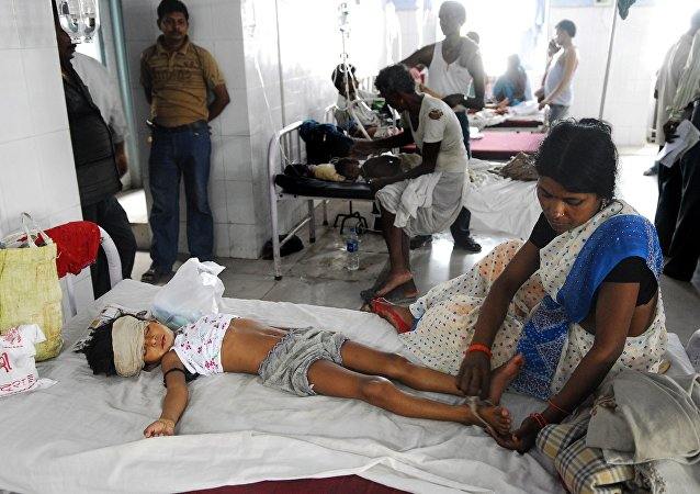 An Indian woman attends to a child lying in a bed of a hospital in Muzzafarapur, some 100kms north of Patna on June 23, 2011.