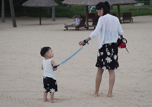 Mère avec son enfant sur la plage. Chine. Image d'illustration