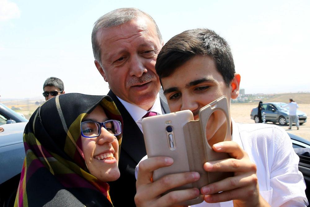 Le président turc Recep Tayyip Erdogan fait une selfie avec des passants pendant une visite au quartier général de la police à Ankara