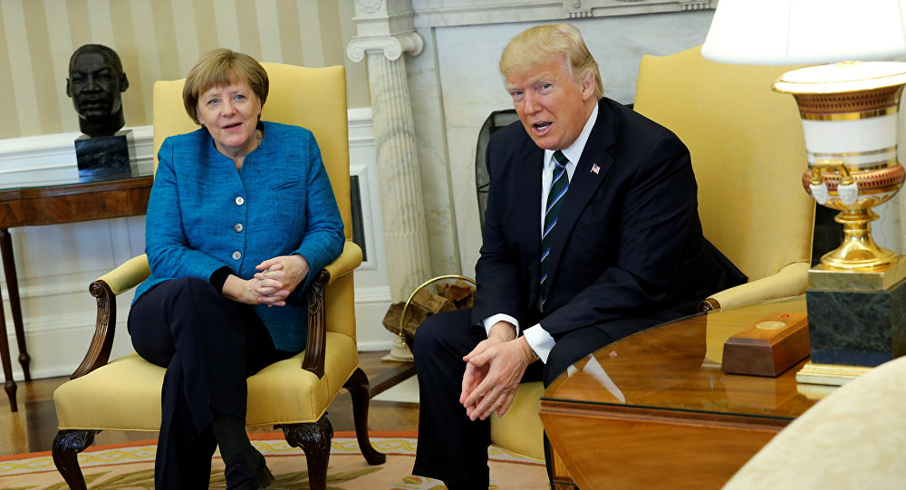 U.S. President Donald Trump and Germany's Chancellor Angela Merkel watch as reporters enter the room before their meeting in the Oval Office at the White House in Washington, U.S. March 17, 2017