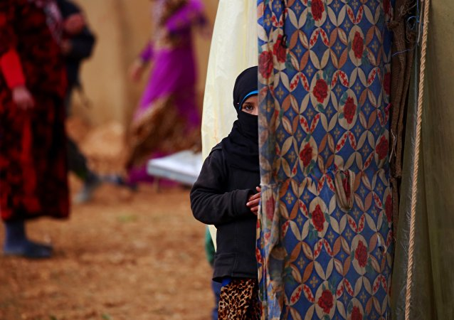 A displaced Syrian woman, who fled her hometown due to clashes between regime forces and the Islamic State (IS) group, stands outside a tent in Kharufiyah, 18 kilometres south of Manbij, on March 4, 2017.
