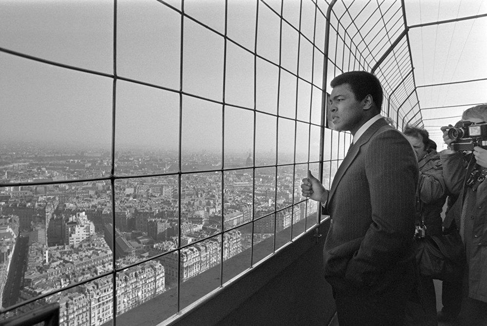Muhammad Ali, champion du monde poids lourds américain (au centre), visite la Tour Eiffel le 5 mars 1976.