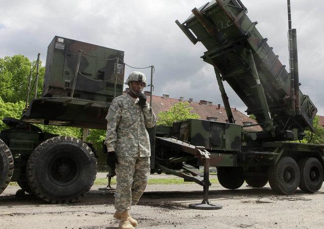 Un soldat américain se trouve à côté d'une batterie de missile sol-air Patriot à une base militaire de Morag, en Pologne