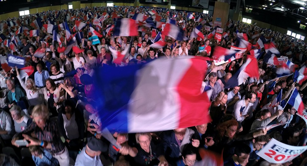 Supporters of presidential election candidate of the French centre-right, Francois Fillon wave flags at a political rally in Paris, France, April 9, 2017,