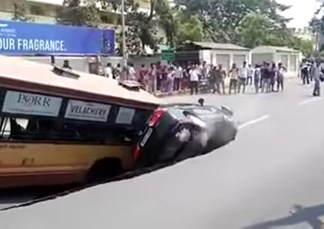 Un bus et une voiture s'enlisent dans un immense nid de poule en Inde