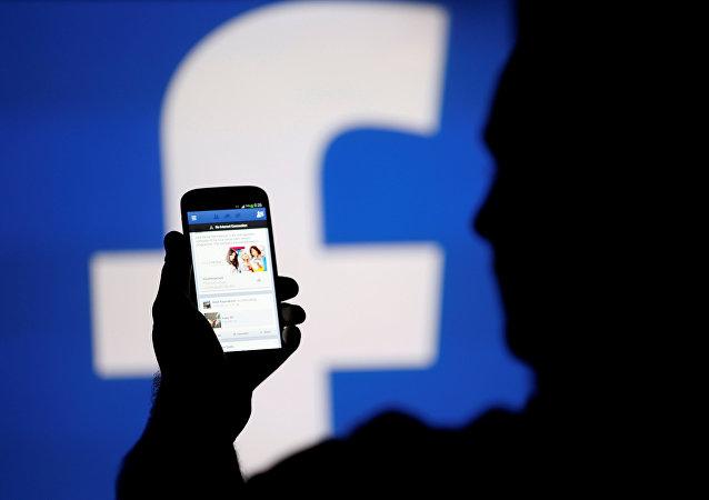 Une silhouette d'un homme en face d'un écran vidéo avec un logo de Facebook