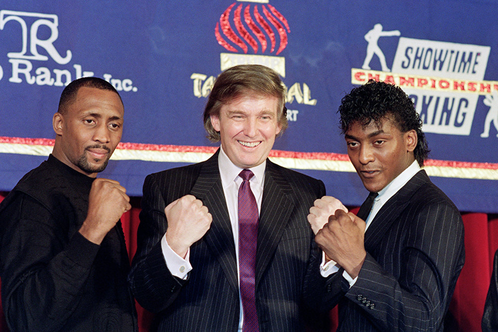 Le milliardaire Donald Trump (au centre), qui a fait une fortune dans l'immobilier, lève les poings le 15 février 1990 à New-York lors de l'annonce d'un combat entre Thomas « The Hitman » Hearns (à gauche) et Michael « The Silk » Olajide (à droite), qui se déroulera le 28 avril 1990 au Trump Taj Mahal Casino d'Atlantic City.