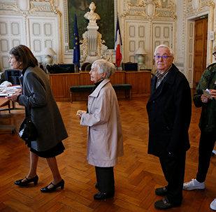 Les gens attendent en ligne pour voter au deuxième tour de l'élection présidentielle française de 2017 à un bureau de vote à Lyon, en France