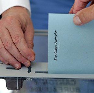 Une personne avec un bulletin dans un bureau de vote lors du premier tour des élections législatives françaises à Nice