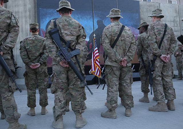 Des militaires américains se tiennent devant un drapeau américain lors d'une cérémonie à l'occasion du treizième anniversaire des attentats terroristes du 11 septembre à Bagram Airfield, en Afghanistan, le jeudi 11 septembre 2014