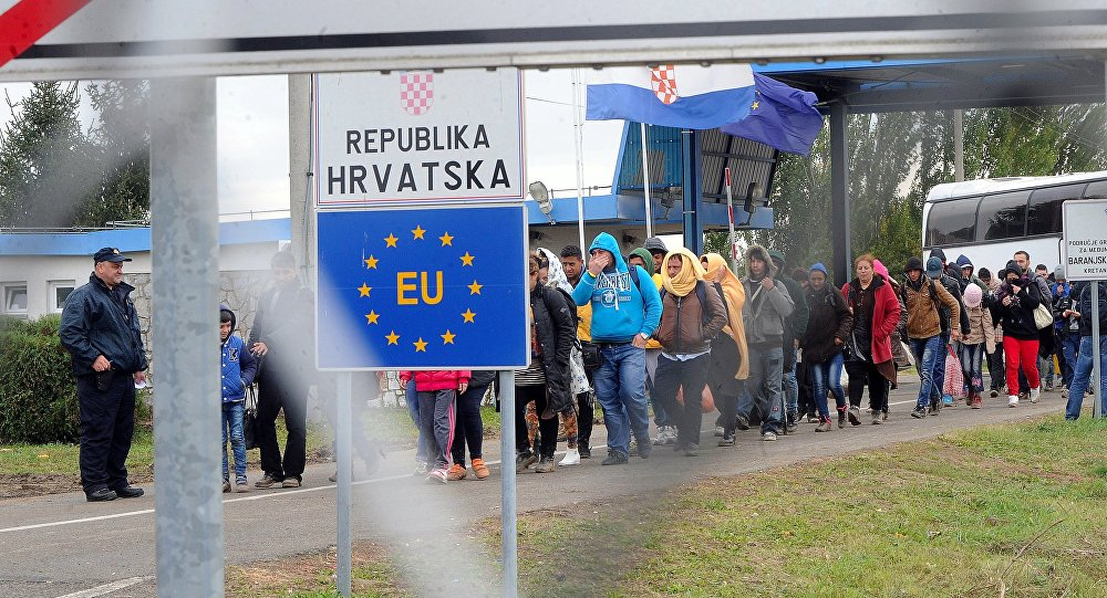 Migrants cross the border at the Hungarian Beremend station on September 30, 2015 as local workers prepare a new transit zone here.