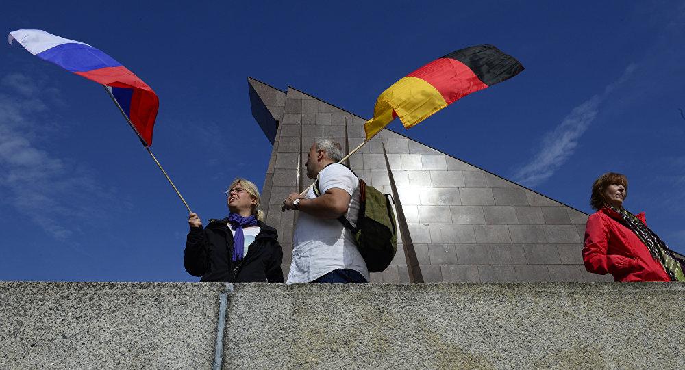 Des touristes avec des drapeaux russe et allemand