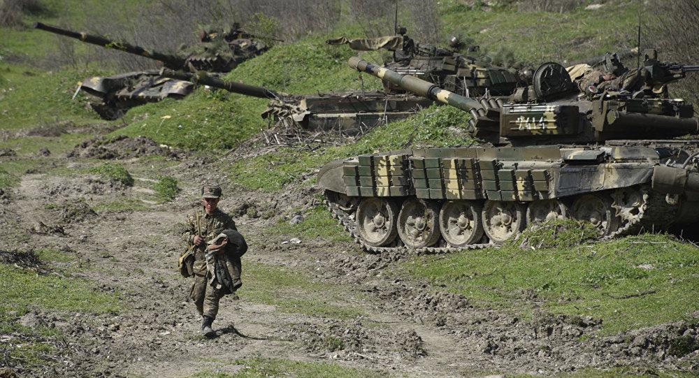 Un soldat de l'armée de défense du Haut-Karabakh se promène devant des chars en position à l'extérieur du village de Mataghis, à environ 70 km au nord de Stepanakert, capitale du Karabakh, le 6 avril 2016