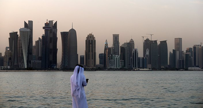 A man looks at his phone on the corniche in the Qatari capital Doha on July 2, 2017.