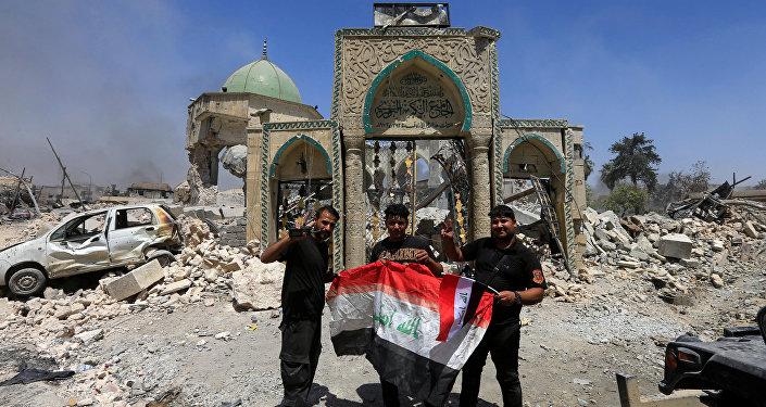 Les membres du Service antiterroriste posent pour une photo avec un drapeau irakien devant les ruines de la mosquée Grand al-Nuri dans la vieille ville de Mossoul, en Irak, le 30 juin 2017