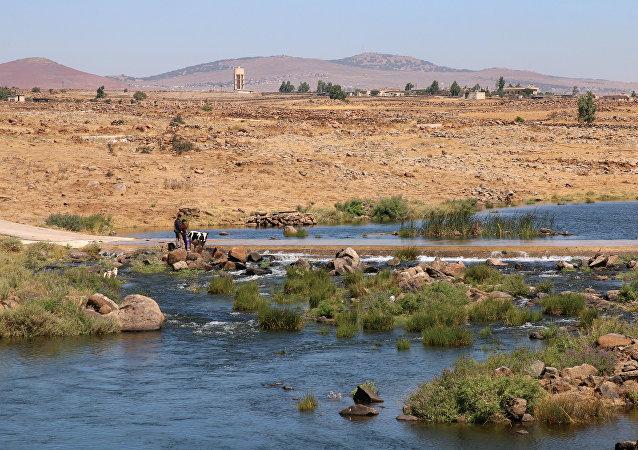 Des agriculteurs syriens nettoient une vache à la rivière Raqqad à Quneitra, en Syrie, le 8 juillet 2017