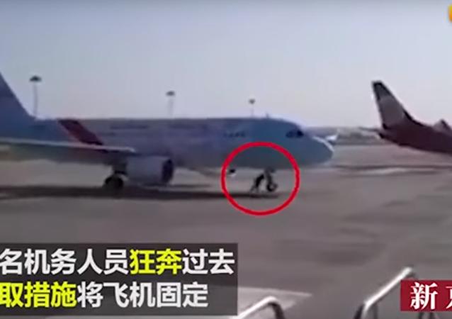 Entre-temps en Chine: un employé d'aéroport arrête un avion à mains nues