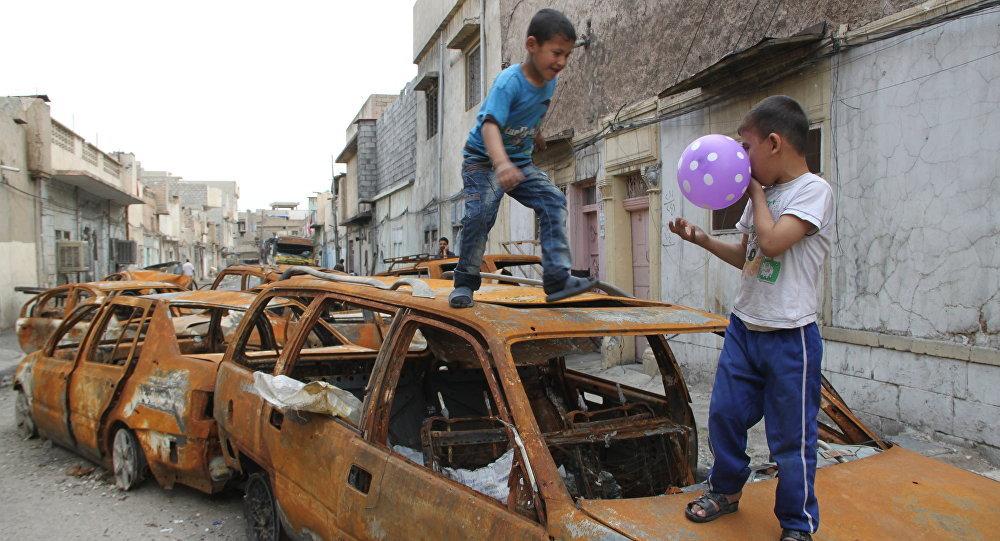 Les enfants jouent sur une voiture brûlée par les terroristes de Daech à Mossoul