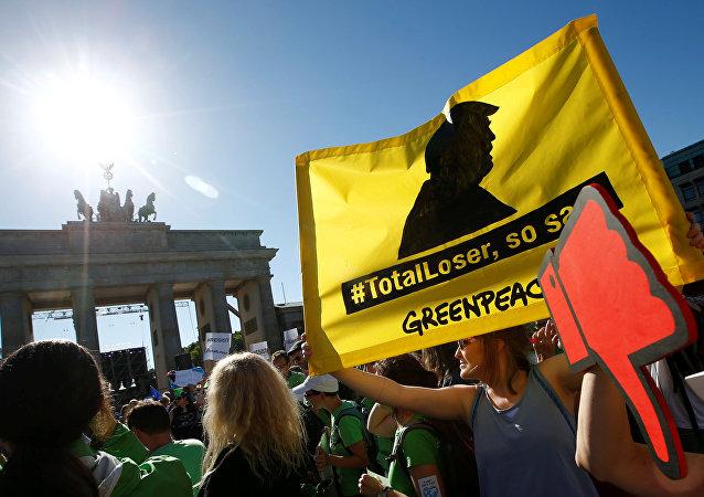 Les gens tiennent des bannières alors qu'ils protestent près de la Porte de Brandebourg, à côté de l'ambassade des États-Unis, contre le retrait des États-Unis de l'accord de Paris sur le changement climatique, à Berlin, en Allemagne, le 2 juin 2017