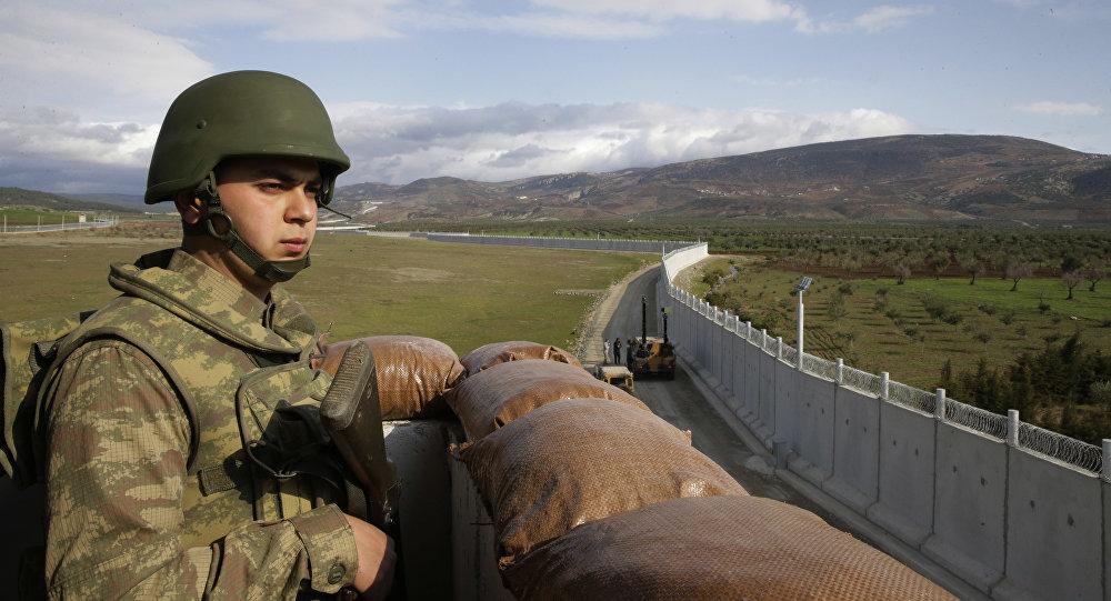 Un soldat de l'armée turque sur un avant-poste près de la ville de Kilis, dans le sud-est de la Turquie, à côté du mur que le pays avait construit pour renforcer la sécurité sur sa frontière avec la Syrie, le 2 mars 2017