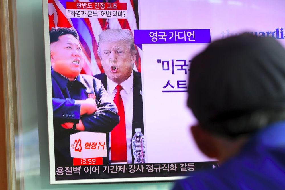 Un homme regarde un journal télévisé dans une gare à Séoul