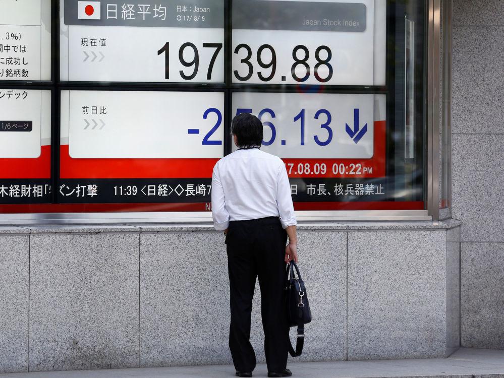 Un homme regarde un panneau sur la façade d'une société de courtage à Tokyo, au Japon