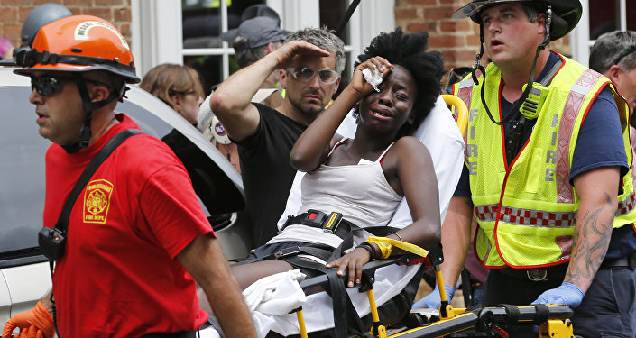 Rescue personnel help an injured woman after a car ran into a large group of protesters after an white nationalist rally in Charlottesville, Va., Saturday, Aug. 12, 2017.
