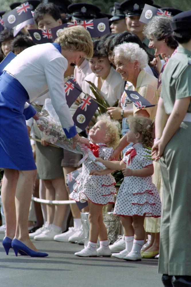 Deux petites sœurs jumelles offrent des fleurs à la princesse Diana lors du dernier jour de sa tournée en Asie, Hongkong, 1989
