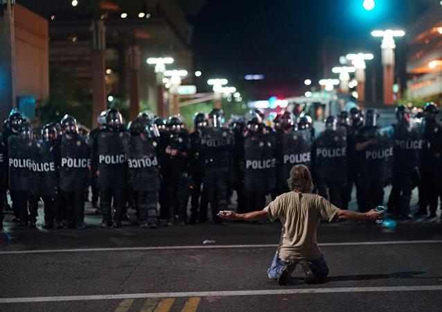 Un manifestant devant les policiers après le rassemblement du président américain Donald Trump à Phoenix, Arizona