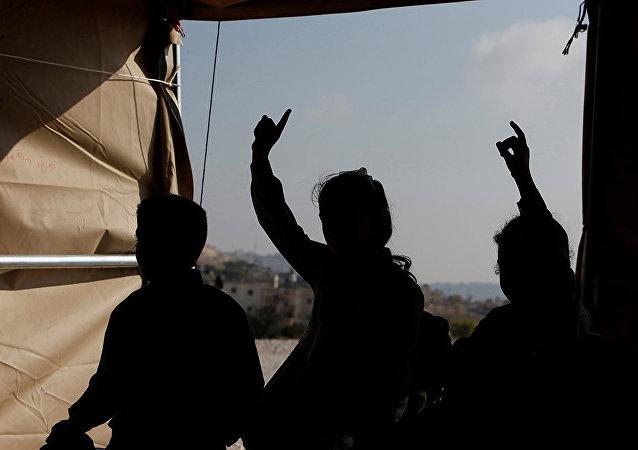 Des enfants palestiniens prennent une leçon à l'intérieur d'une tente