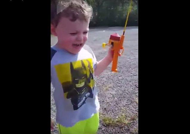 Un serpent cruel vole le poisson d'un enfant. Quelle honte!