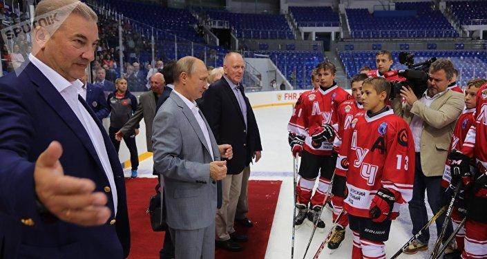 À droite de M.Poutine - le joueur du hockey canadien Red Berenson, à gauche - le président de la Fédération du hockey de la Russie Vladislav Tretiak