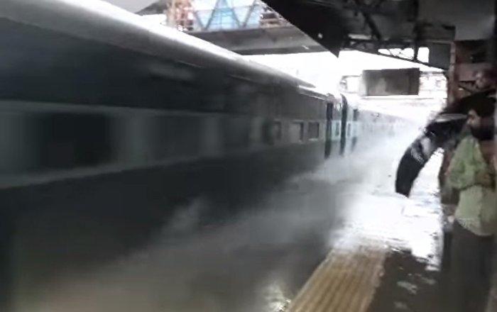 Un train traverse à pleine vitesse une gare inondée et arrose les passagers qui attendent sur le quai